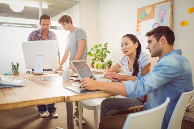 Creative business team gathered around laptops. In the office stock photo
