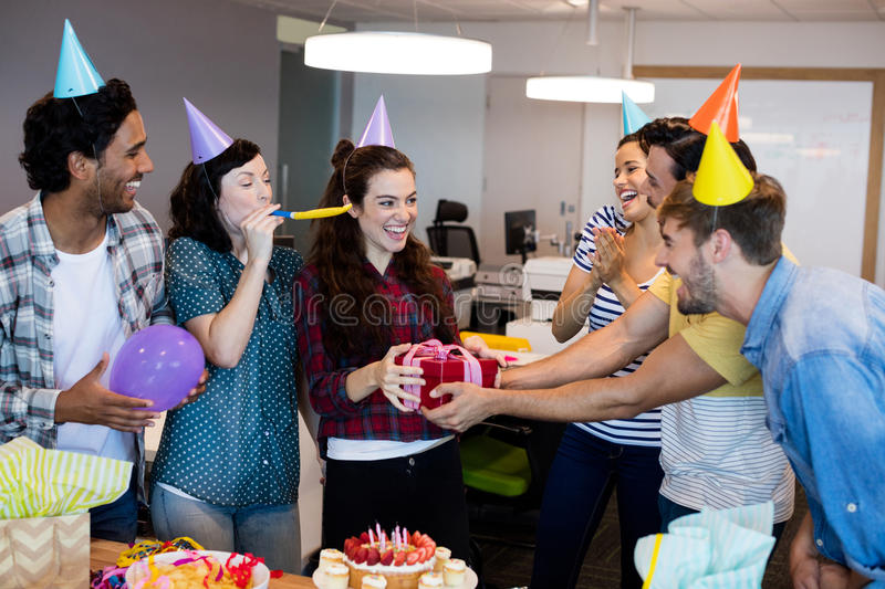 Creative business team giving a gift to their college on her birthday. At office stock images