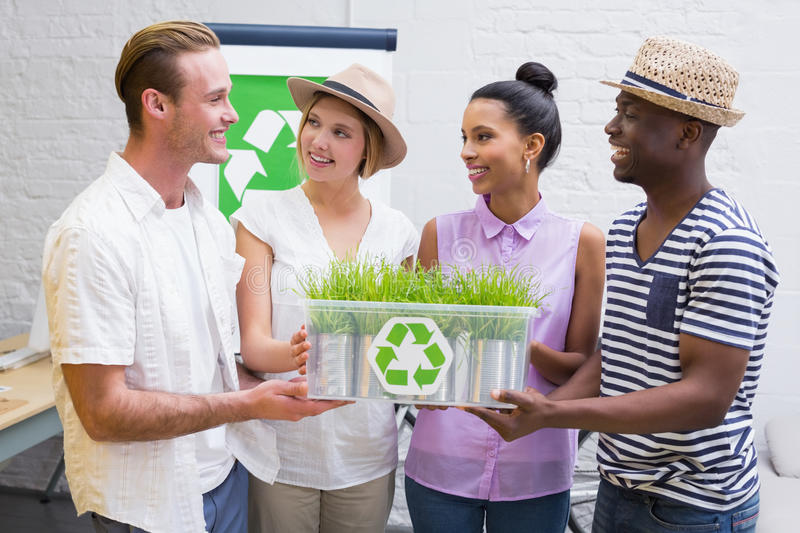 Creative business team holding plant with recycling symbol. Portrait of creative business team holding plant with recycling symbol in meeting stock photo