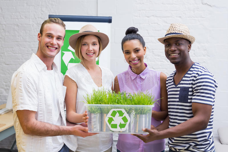 Creative business team holding plant with recycling symbol. Portrait of creative business team holding plant with recycling symbol in meeting royalty free stock photos