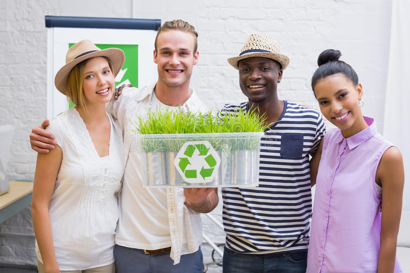 Creative business team holding plant with recycling symbol. Portrait of creative business team holding plant with recycling symbol in meeting royalty free stock photography