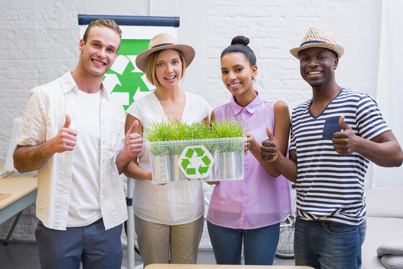 Creative business team holding plant with recycling symbol. Portrait of creative business team holding plant with recycling symbol in meeting royalty free stock images