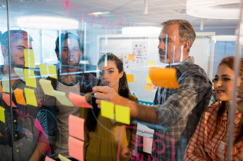 Creative business team looking at sticky notes on glass window royalty free stock photography