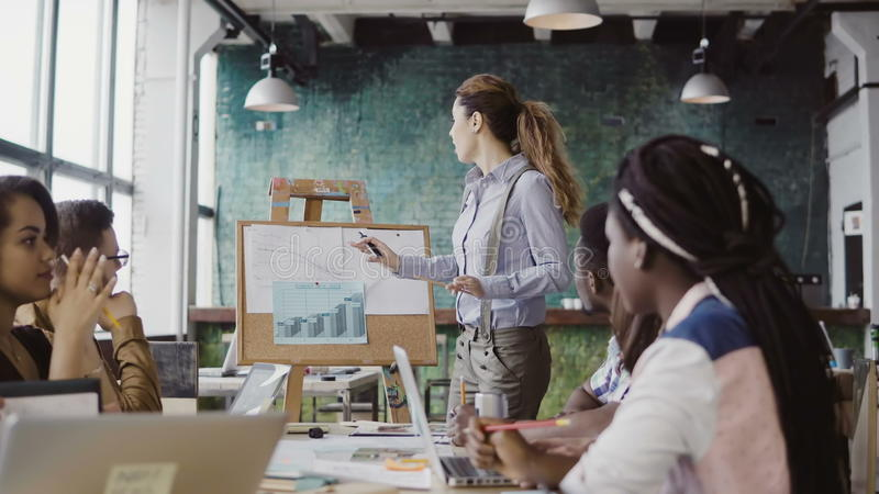 Creative business team meeting at modern office. Manager female presenting financial data, motivates team to work. stock photography