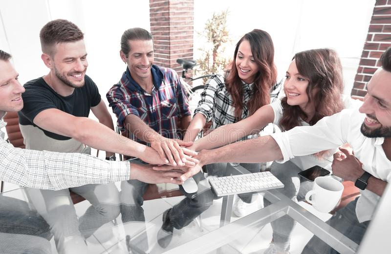 Creative business team putting hands together at the office stock photography