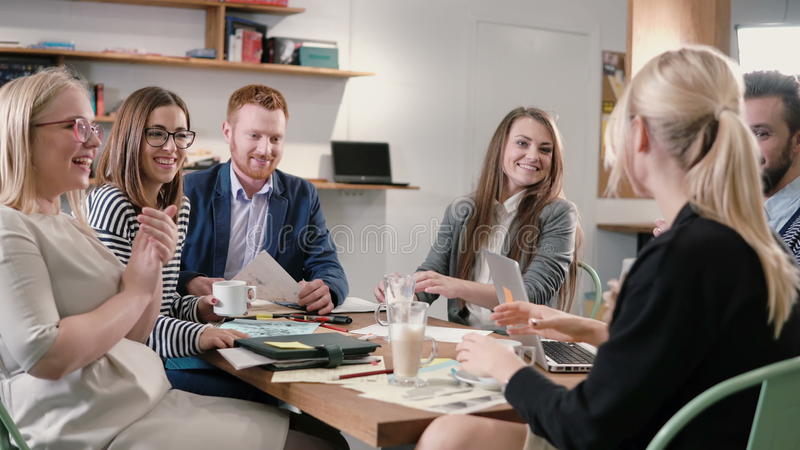 Creative business team at table in a modern startup office. female speaker offers a great idea and the team supports her. Creative business team sitting around stock photo