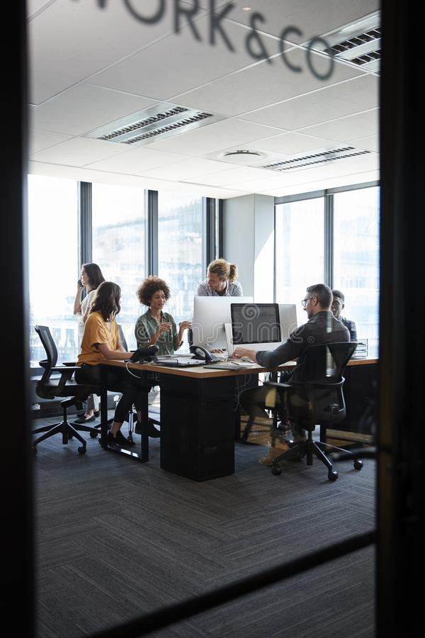 Creative business team working in a casual office, seen through glass wall with text on it, vertical royalty free stock photos