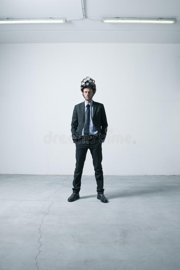 Creative businessman with steampunk helmet. Confident businessman standing in an empty room with futuristic helmet stock images