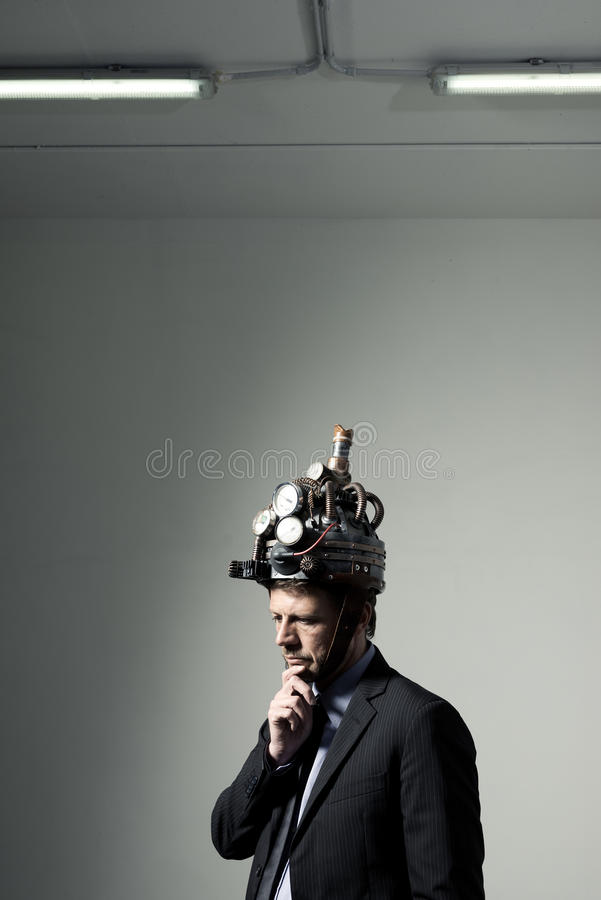 Creative businessman with steampunk helmet. Confident businessman thinking with hand on chin wearing steampunk helmet stock image