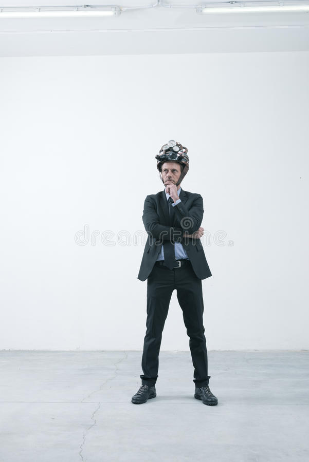 Creative businessman with steampunk helmet. Confident businessman thinking with hand on chin wearing steampunk helmet royalty free stock photo