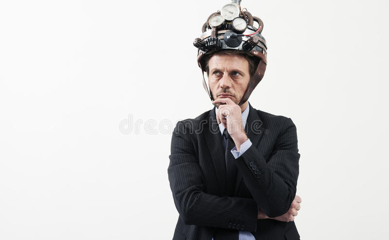 Creative businessman with steampunk helmet. Confident businessman thinking with hand on chin wearing steampunk helmet on white background stock images