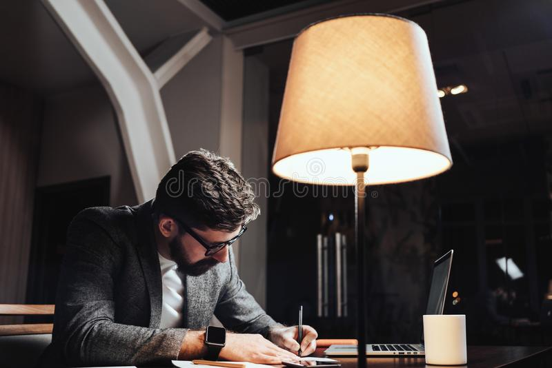 Creative businessman working with paper documents and contemporary laptop at late evening in loft office. Bearded young man sits b royalty free stock photography