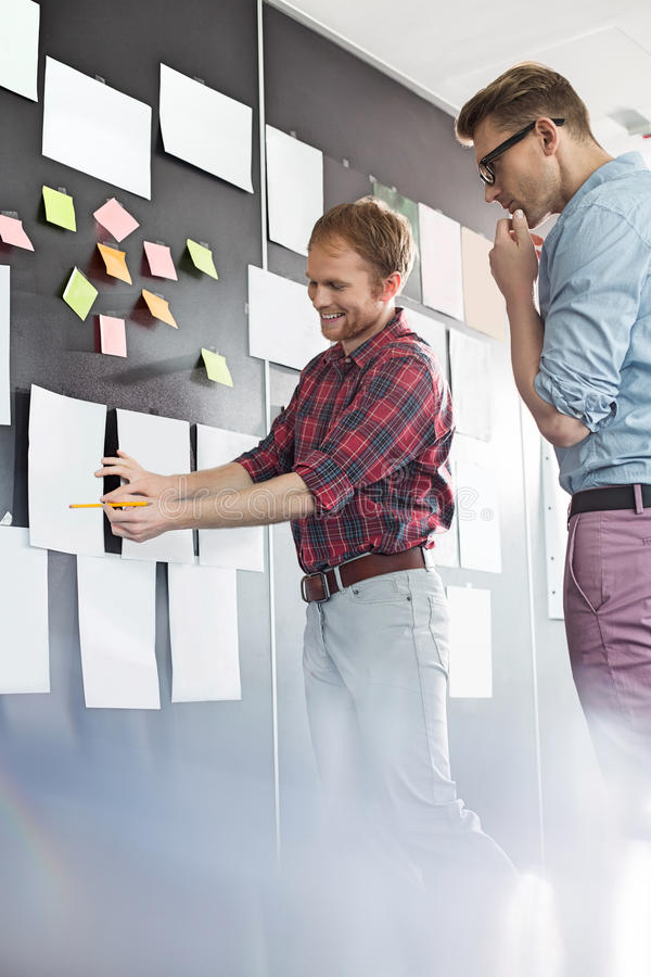 Creative businessmen discussing over document on wall in office royalty free stock photo