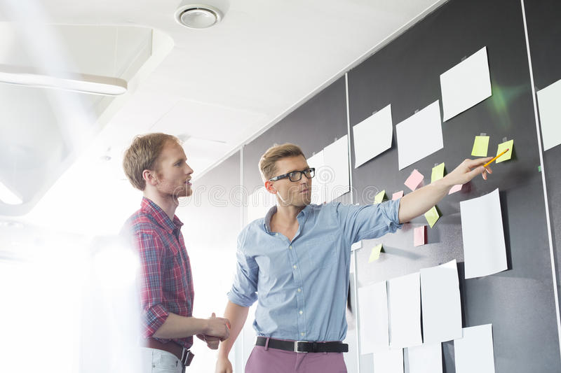 Creative businessmen discussing over sticky paper on wall in office royalty free stock image