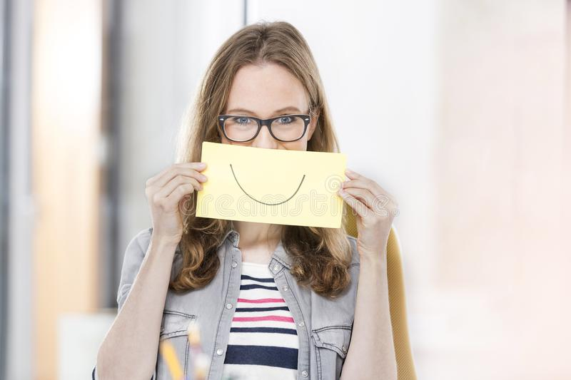 Creative businesswoman holding paper with smile drawn on it stock photos