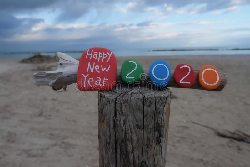 Happy New Year 2020 with a creative colored stones composition on a wooden pole with beach background vector illustration
