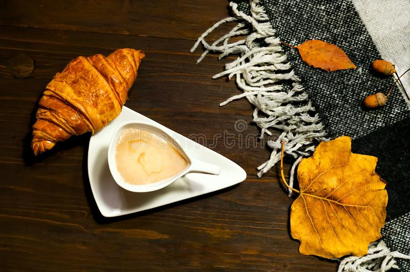Creative ceramic cup of coffee with milk and croissant on wooden background with plaid, concept of coziness and warmth.Copy space stock photo