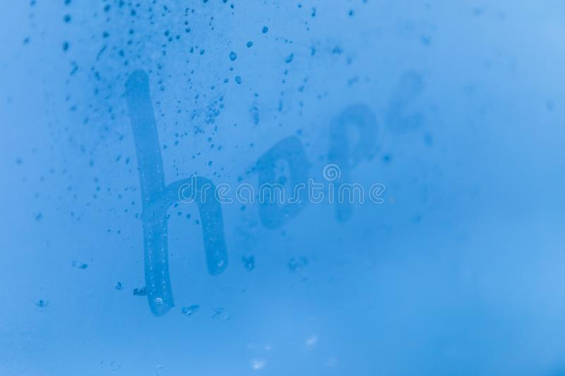 The creative child inscription hope on the blue evening or morning window glass royalty free illustration