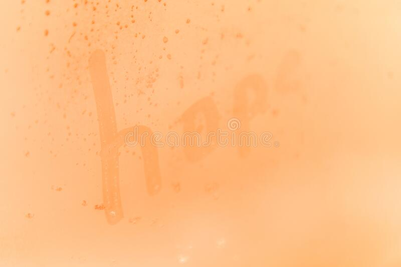 The creative child inscription hope on the orange or pink evening or morning window glass royalty free stock photo