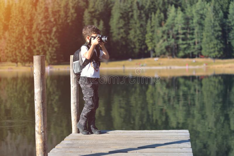 Creative child, kid photographer a little boy with a camera taking landscape pictures near la lake stock photography