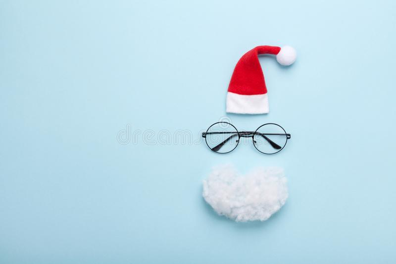 Creative christmas composition. Greeting card, invitation or flyer. Santa hat, beard and glasses on blue background top view. royalty free stock photography