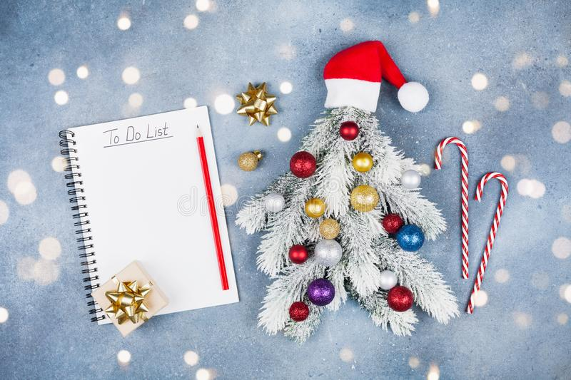 Creative Christmas fir tree decorated Santa hats, gift box and colorful balls with do list on blue background top view. Flat lay. royalty free stock image
