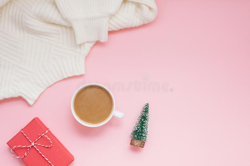 Creative christmas flat lay overhead top view coffee milk latte cup and present gift box on millennial pink background copy space stock photography