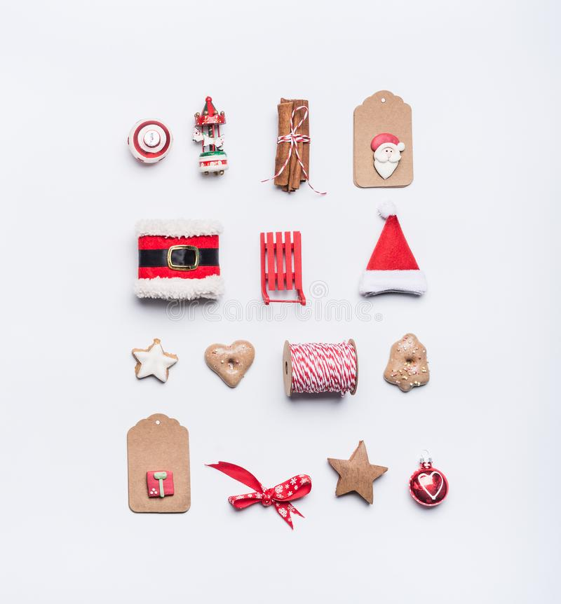 Creative Christmas layout made of craft paper tags, cookies, red Christmas winter decoration: Santa hat, sleigh, cinnamon sticks o. N white desk background, top stock photo