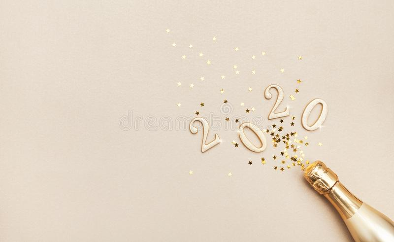 Creative Christmas and New Year composition with golden champagne bottle, confetti stars and 2020 numbers. Flat lay royalty free stock image