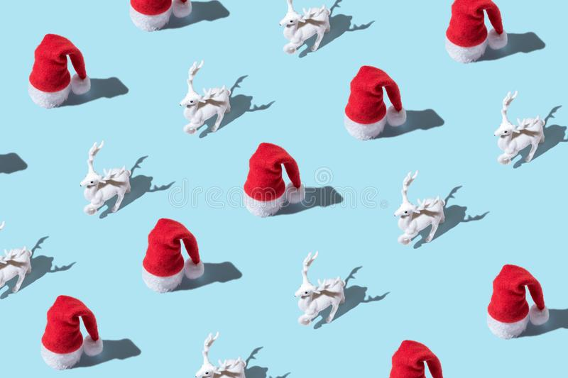 Creative Christmas pattern made of Christmas reindeer and Santa hat on bright blue background. Minimal Christmas or New Year stock image