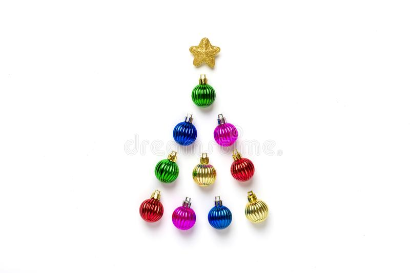 Creative Christmas tree made of colorful bauble and golden star decoration isolated on white background. stock images