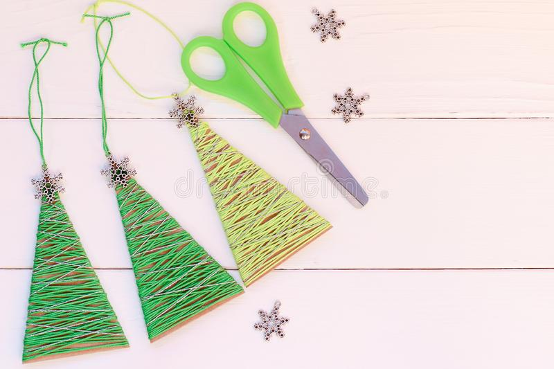 Creative Christmas trees decor on a wooden background. Cheap idea for recycled crafts and Christmas home decorating. Simple recycled Christmas decorations. Ideas stock photo