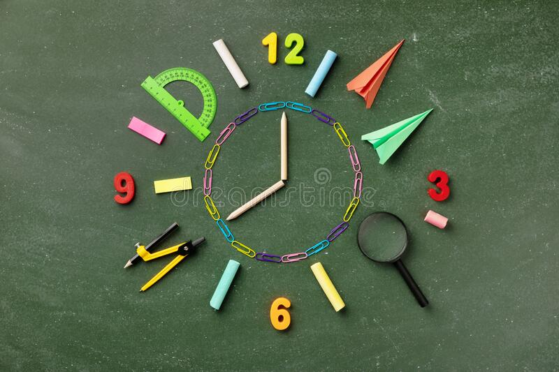 Creative clock face from colorful school supplies on blackboard top view and flat lay. Back to school and time to study concept royalty free stock image
