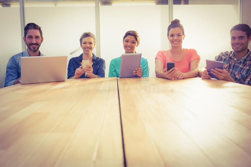Creative colleagues with laptop and digital tablet smiling at camera stock photo
