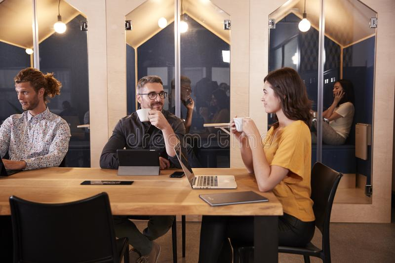 Creative colleagues sitting at a table drinking coffee and talking in their office canteen, close up royalty free stock photo