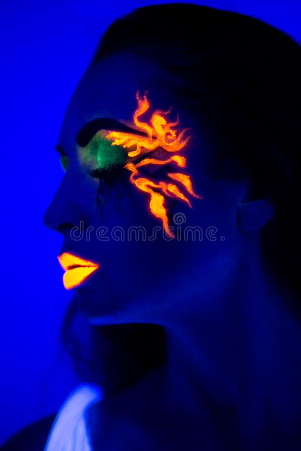 Woman uv light neon make up beauty. Creative colorful makeup neon, glowing painting on face ultraviolet picture, shiny orange fire on blue body. girl portrait royalty free stock images