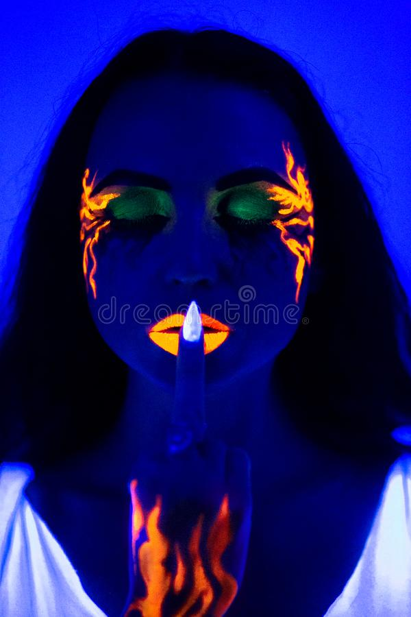Woman uv light neon make up beauty. Creative colorful makeup neon, glowing painting on face ultraviolet picture, shiny orange fire on blue body. girl portrait royalty free stock photos