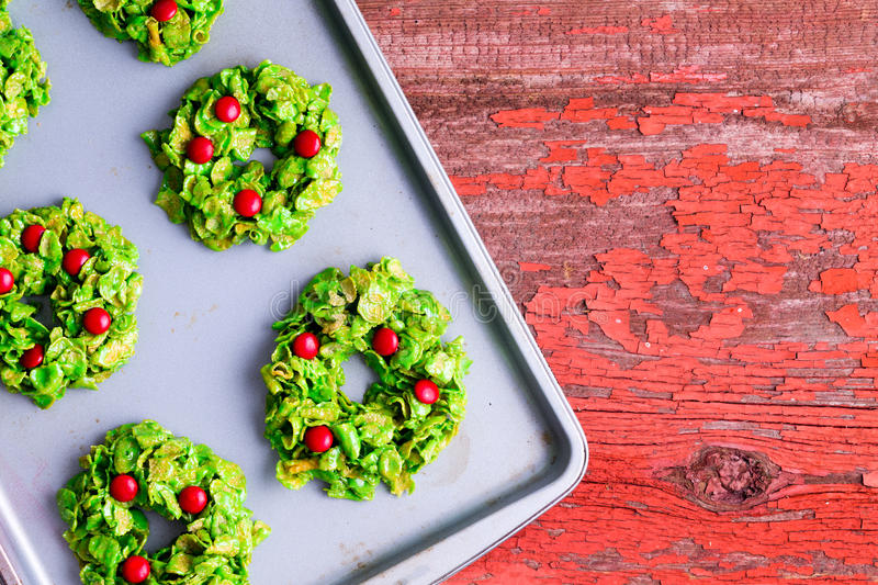 Creative colorful Xmas wreath cookies. Made with green cornflakes and candy pearls cooling on an oven tray on a rustic red table to celebrate the Christmas stock image
