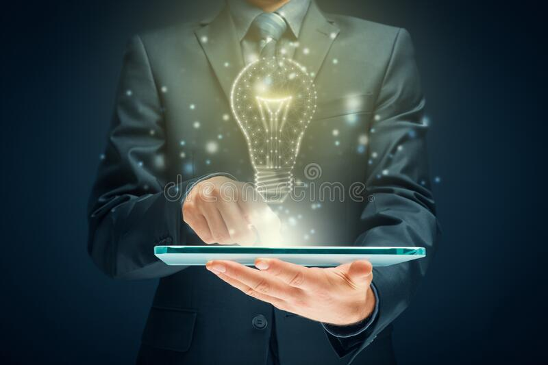 Turn on creativity, idea and intelligence concepts. Creative company give you their creativity and ideas. Hands with digital tablet and graphics light bulb stock photography