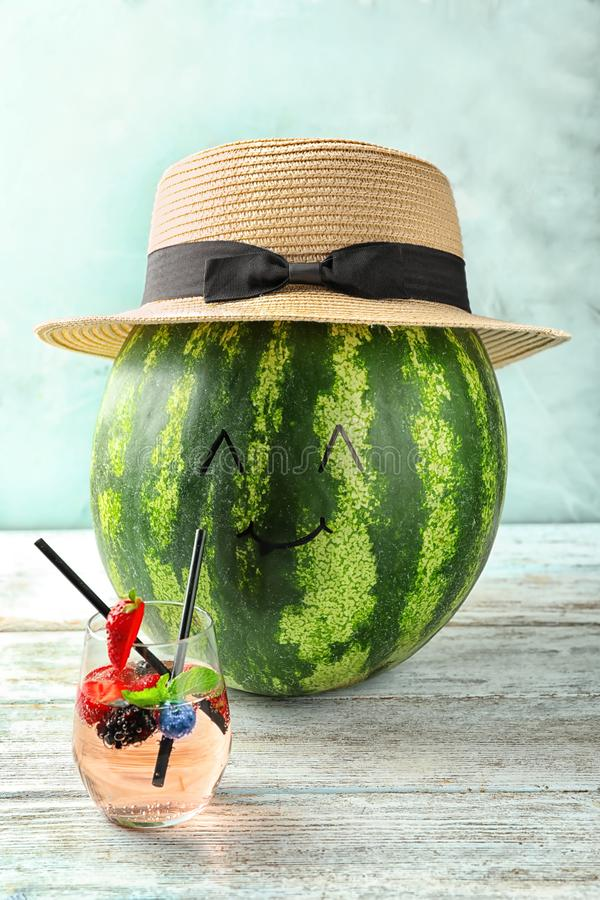 Creative composition with delicious watermelon in hat and glass of cocktail on wooden table stock images