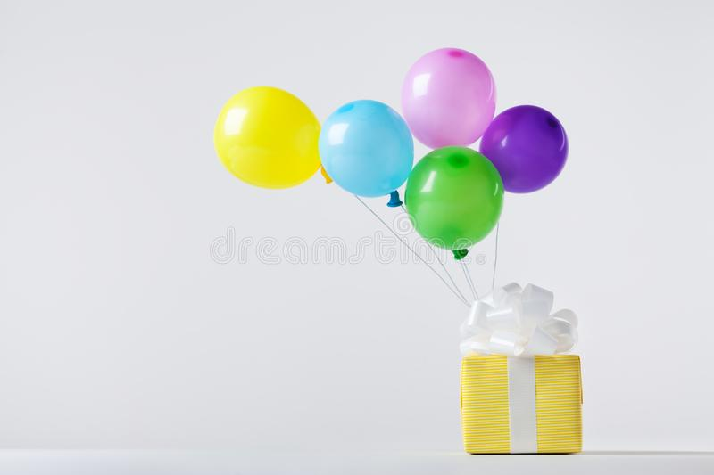 Creative composition with gift box and flying colorful balloons. Birthday or party concept royalty free stock photos