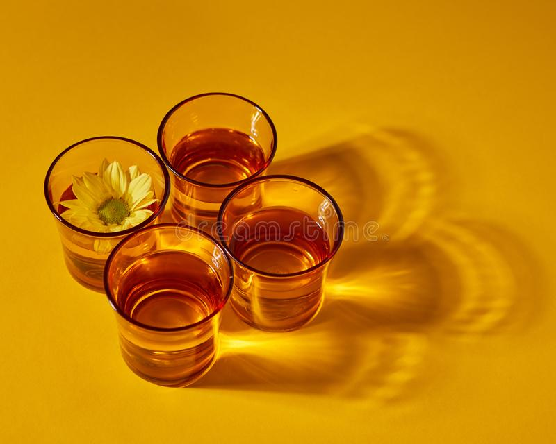 Set with yellow glasses with water and flower with shadows on a yellow paper background. Top view royalty free stock photography