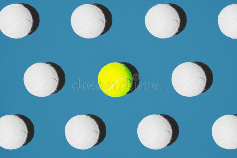 Creative composition made with yellow tennis ball and white balls on blue background. royalty free stock photo