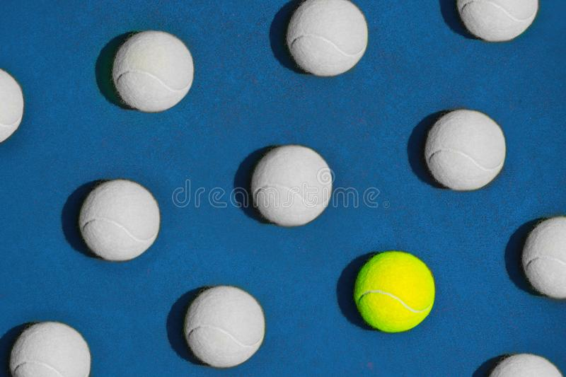 Creative composition made with yellow tennis ball and white balls on blue background. royalty free stock photos