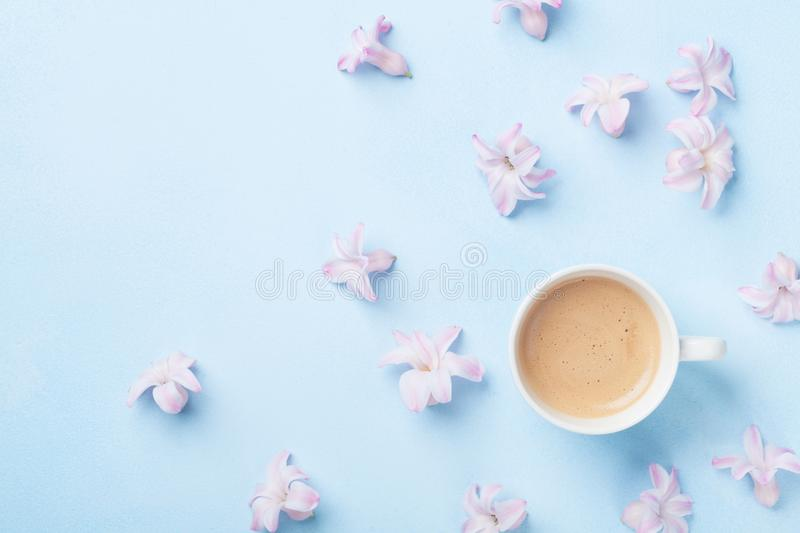 Creative composition with morning coffee and pink flowers on blue pastel background top view. Flat lay style. royalty free stock photos