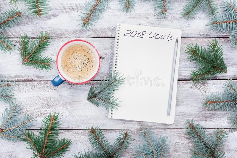 Creative composition of notebook with goals for 2018, fir tree and cup of coffee on wooden table top view. Planning concept. royalty free stock photos