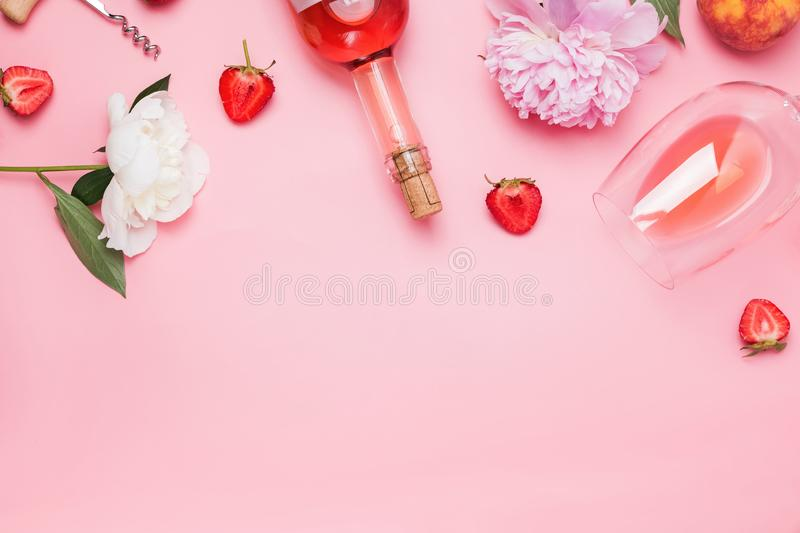 Creative composition with rose wine and delicious strawberries on the pink background stock photography