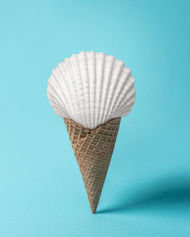 Creative composition with seashell and ice cream cone on pastel blue background. Summer minimal concept stock images