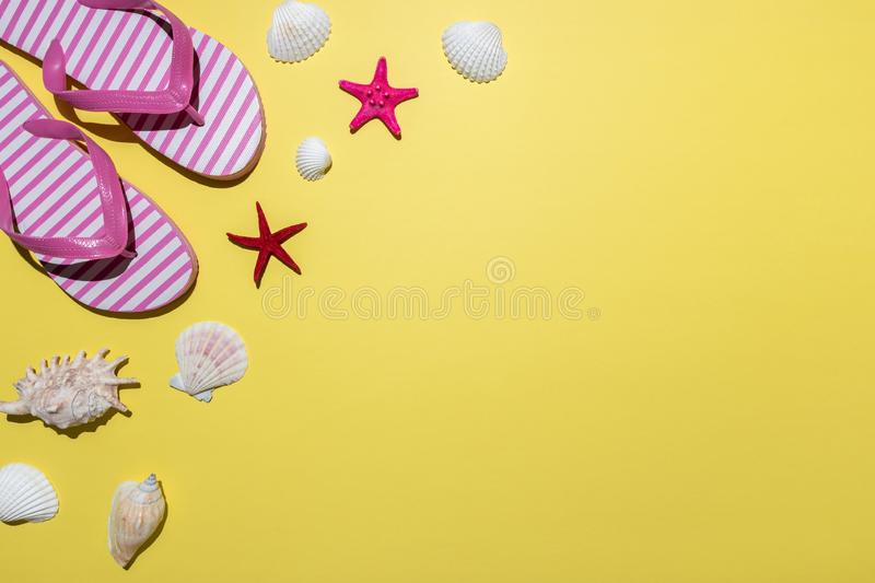 Creative composition with seashells and beach slippers on bright yellow background. Summer minimal concept.  stock image