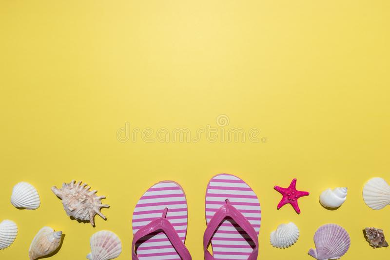 Creative composition with seashells and beach slippers on bright yellow background. Summer minimal concept.  royalty free stock photography